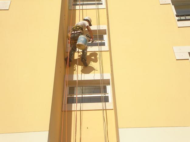 Las pinturas exteriores de fachadas pueden ejecutarse con ayuda de andamios o con descuelgue por rapel (técnica opcional de trabajo en altura, combinando las técnicas más avanzadas de acceso a lugares elevados y en ambientes confinados con uso de cuerdas y equipamiento específico de descenso y ascenso)